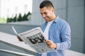 handsome-man-reading-newspaper-street_23-2147694649